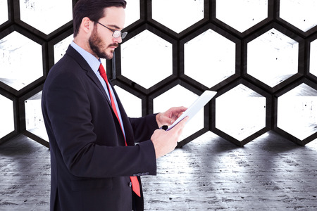 Businessman scrolling on his digital tablet against hexagon room photo