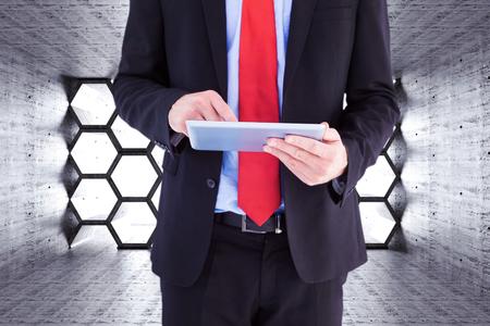 scrolling: Businessman scrolling on his digital tablet against hexagon room