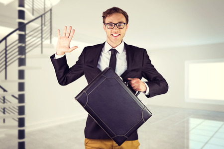 Young geeky businessman holding briefcase against digitally generated room with winding stairs photo
