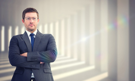 frowning: Frowning businessman looking at camera against curved white room