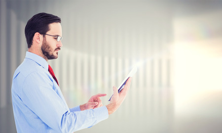 scrolling: Businessman scrolling on his digital tablet against white curved room Stock Photo
