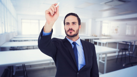 salle classe: Homme d'affaires tenant une craie et d'�crire quelque chose contre la salle de classe vide Banque d'images