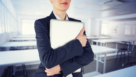 class room: Businesswoman holding laptop against empty class room