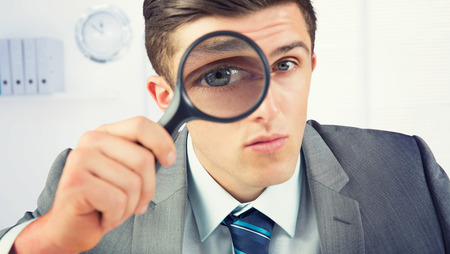 magnifying glass man: Businessman looking through magnifying glass against a empty office with a laptop