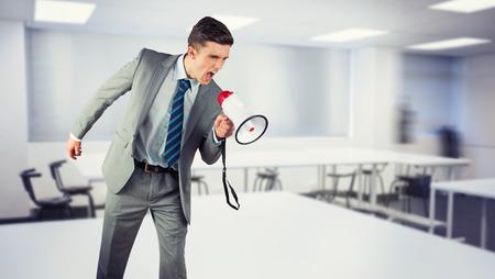 businessman using a megaphone: Businessman shouting through megaphone against empty class room