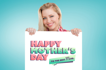 beaming: Woman beaming while holding a blank sign against blue vignette background Stock Photo