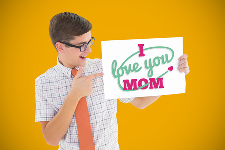 Geeky hipster smiling and showing card against yellow background with vignette photo