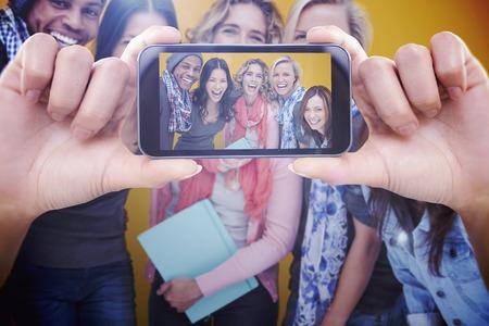 riendose: Mano que sostiene tel�fono inteligente que muestra contra alegre grupo de amigos riendo juntos Foto de archivo