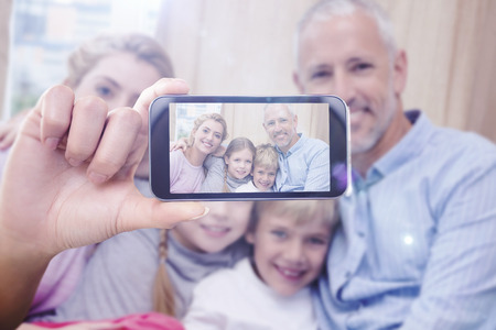 father and son holding hands: Hand holding smartphone showing against happy parents with their children on sofa Stock Photo