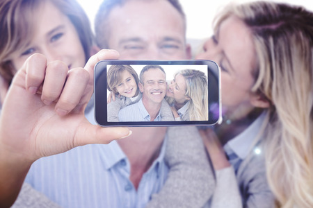mid adult: Hand holding smartphone showing against happy father carrying his son and his wife on his back