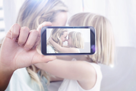 hand rubbing: Hand holding smartphone showing against mother and daughter rubbing noses on sofa