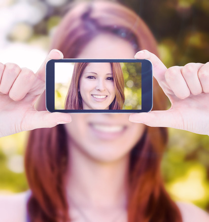 female hand: Hands holding smartphone against portrait of a pretty redhead smiling