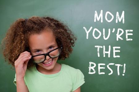 green chalkboard: Cute pupil tilting glasses against green chalkboard Stock Photo