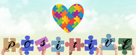 Hands holding up positive jigsaw pieces against blue sky photo
