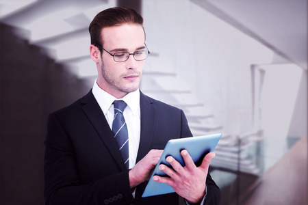 Unsmiling businessman using tablet pc against stylish modern home interior with staircase photo