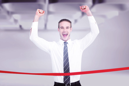 win win: Businessman crossing the finish line and cheering against white abstract room Stock Photo