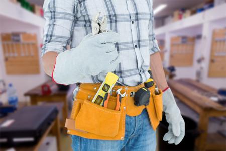 waist belt: Technician with tool belt around waist holding pliers against workshop Stock Photo