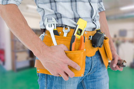 Cropped image of technician with tool belt around waist against workshop Stock Photo