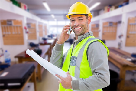 construction hat: Happy architect against workshop