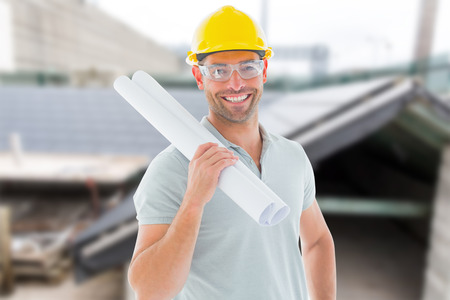 Architect with plan against workshop photo