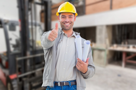 construction work: Architect showing thumbs up against workshop