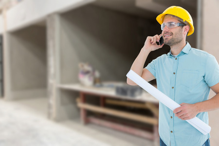 Male architect with blueprint talking on mobile phone against workshop photo