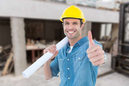 thumbs up man: Architect holding blueprint while gesturing thumbs up against workshop