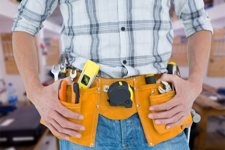 Cropped image of technician with tool belt around waist against workshop photo