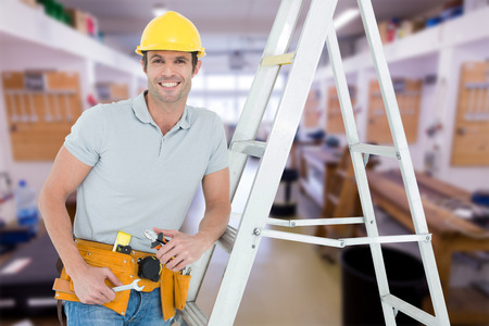 step ladder: Worker holding tools while leaning on step ladder against workshop Stock Photo