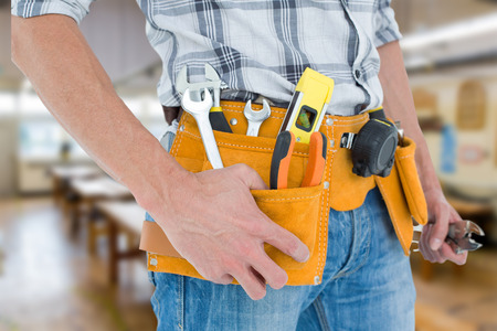 waist belt: Cropped image of technician with tool belt around waist against workshop Stock Photo