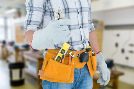 waist belt: Technician with tool belt around waist holding pliers against workshop Stock Photo