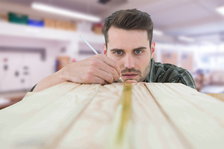 carpintero: Carpintero marcando en tablón de madera contra el taller Foto de archivo