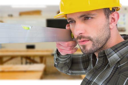 spirit level: Carpenter using spirit level  against workshop