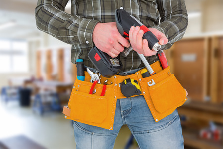 power drill: Manual worker holding gloves and hammer power drill  against workshop Stock Photo