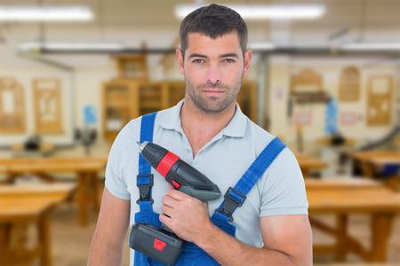 power drill: Portrait of confident carpenter holding power drill against workshop