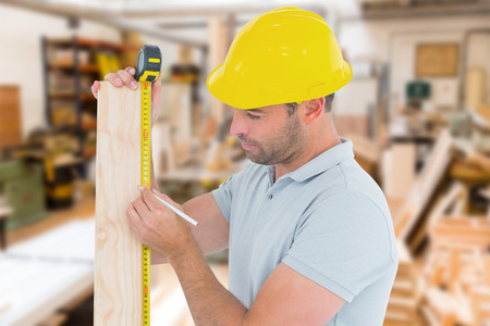 Carpenter using measure tape to mark on wooden plank against workshop photo