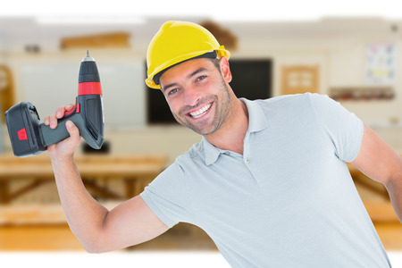 power drill: Smiling repairman holding power drill against workshop Stock Photo