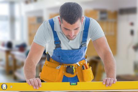 spirit level: Worker using spirit level against workshop Stock Photo