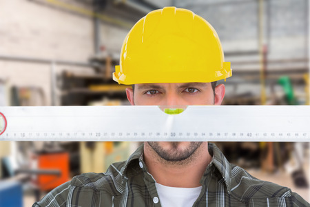 spirit level: Handyman looking at spirit level against workshop