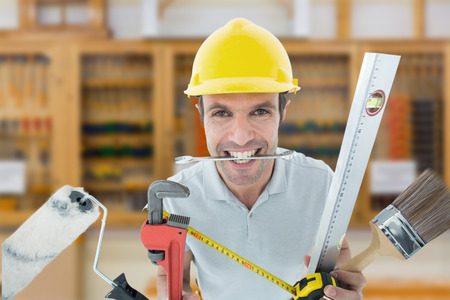 happy worker: Happy worker with various equipment against workshop Stock Photo