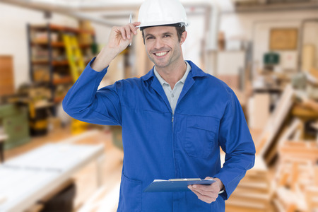 clip board: Happy supervisor wearing hard hat while holding clip board against workshop Stock Photo