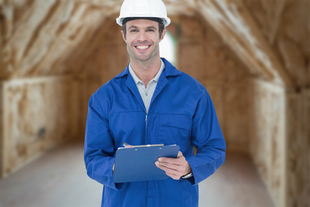Confident supervisor writing notes against room in house under construction photo