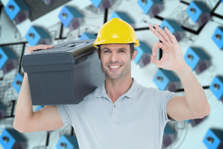 Worker carrying tool box on shoulder while gesturing OK sign against blue 3d houses in an estate order photo