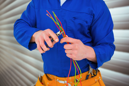 Electrician cutting wire with pliers against grey shutters photo