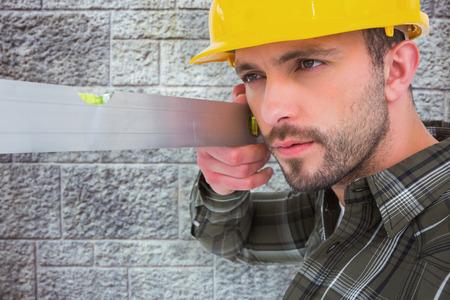 spirit level: Carpenter using spirit level  against grey brick wall