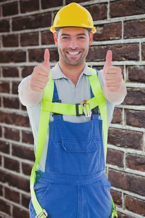 safety gear: Builder in safety gear against red brick wall