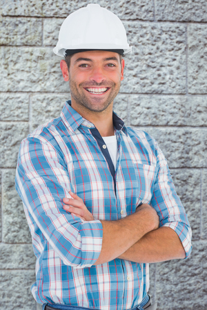hardhat: Confident manual working wearing hardhat against grey brick wall Stock Photo
