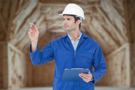 clip board: Supervisor inspecting while holding clip board against room in house construction site Stock Photo