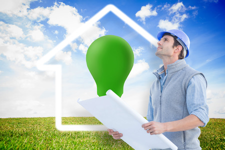 green light bulb: Architect with blueprint against green light bulb with white house outline Stock Photo