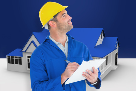 work from home: Male supervisor looking up while writing on clipboard against blue house standing with energy rating